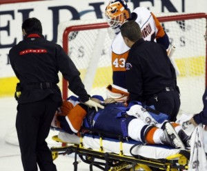 New York Islander's Kyle Okposos is carried off on a stretcher after being hit by Calgary Flame's Dion Phaneuf.