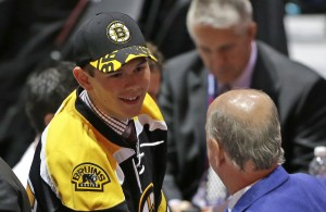 Jeremy Lauzon greets team executives after being chosen by the Boston Bruins. during the second round of the NHL hockey draft, Saturday, June 27, 2015, in Sunrise, Fla. (AP Photo/Alan Diaz)